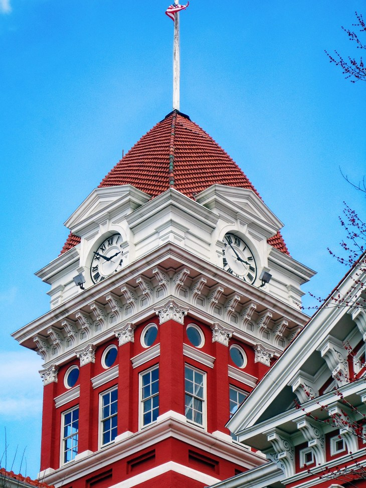 The courthouse features an impressive clock tower which rises nearly 130 feet tall towards a terra-cotta dome.